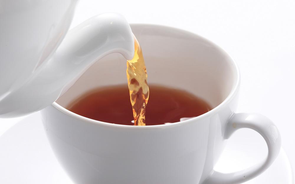 ティーポットから紅茶をティーカップに注ぐ